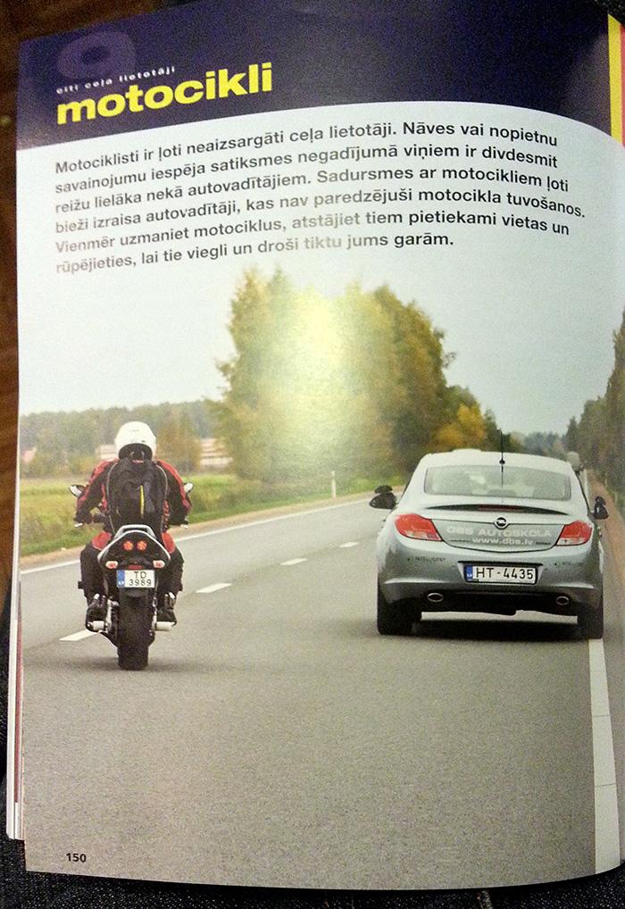 Komiska kļūda — Drošas braukšanas skolas automašīna pārkāpj ceļu satiksmes noteikumus, lai parādītu rūpes par motociklistu.