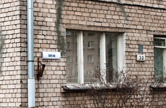 Jaunā ielas nosaukuma zīme blakus nedaudz vecākai mājas numura zīmei.