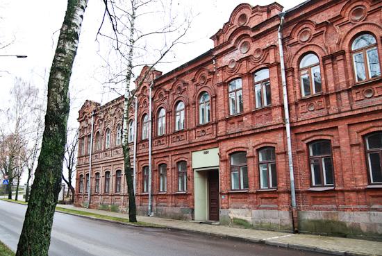 Daugavpils apbūvei tipisko sarkano ķieģeļu māja ar sadirstu galveno ieeju.