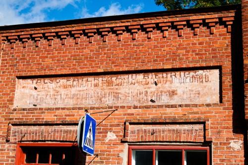 Talsi. Uzraksts (izkārtne) uz vecas ķieģeļu ēkas.